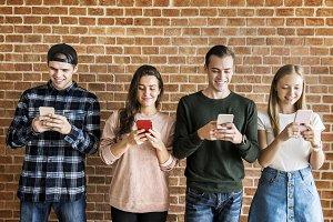 Happy friends using smartphones