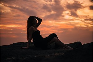 silhouette of a sitting woman at sunset