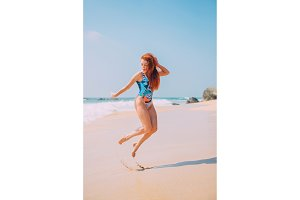 happy young woman is jumping on the beach