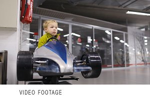 Little boy driving a racing car