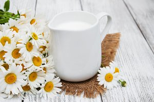 jug with milk  and chamomile flower