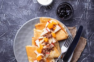 Pancakes crepes with different fruits and chocolate