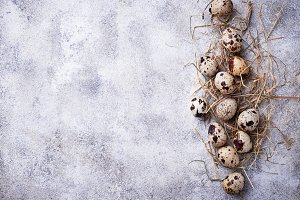 Quail eggs and straw on light background