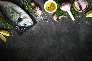 Fresh fish Dorado and ingredients for cooking at black.