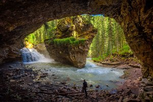 Hiker watching Johnston Creek from a cave