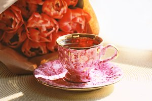 Cup of fresh tea and bouquet