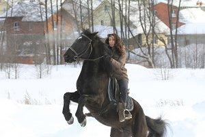 Young woman riding on black horse in snowy countryside