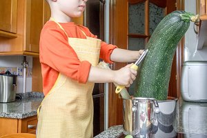Cute child chef cooking big zucchini