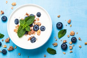 Greek yogurt granola and blueberries on blue table.
