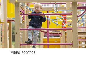 Cute little boy climbing jungle gym