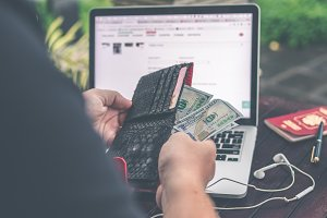 Man doing online shopping with credit card, laptop and luxury snakeskin python wallet. Man online shopping concept.