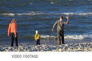 Family of three on pebble beach.