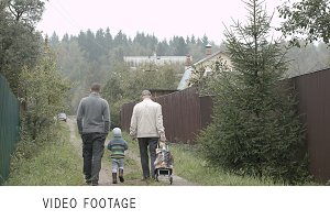 Two men and boy walking countryside