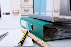 Folder file, note and pen on desk.