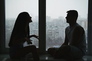 Young family couple sitting on the windowsill, emotionally talking, arguing and gesticulating