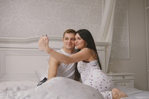 Happy cheerful loving couple making selfie in bed, young attractive guy and girl sitting in pajamas