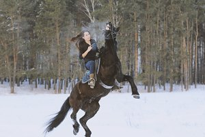 Young attractive woman riding on black horse in snowy forest