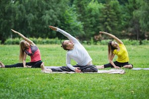 A group of yoga sportsmen performs breathing exercises in park