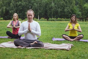 Yoga sportsmen in park - athletes in lotus pose