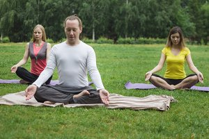 Yoga athletes in park - sportsmen in lotus pose