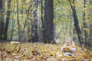 Little daughter plays with yellow leaves in autumn park - the girl is happy and laughing - wide angle