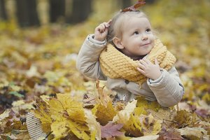 Little daughter plays with yellow leaves in autumn park - the girl is happy and laughing