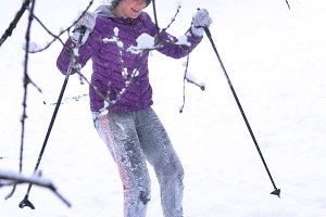 teenager girl skiing in the park in knitted hat dawn jacket with ski