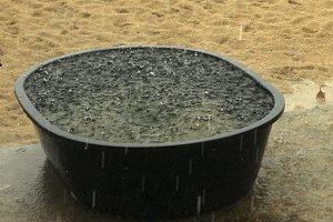 raining on sandy beach with water full basin