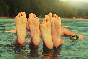 kids teenager feet close up photo in the sea on the tropical