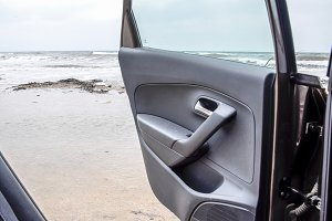 An open car door against the sea. St