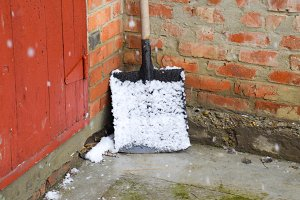 A snow shovel in the snow and stands