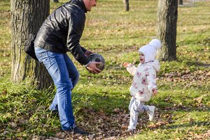 Dad and daughter are playing ball. W