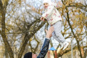 joyful father tosses his daughter up