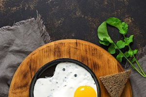 Scrambled eggs in a frying pan with rye bread.