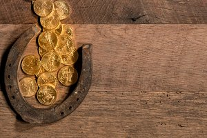 Pile of gold coins flowing into horseshoe for St Patricks Day