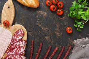 Cutting various sausages with tomatoes, baguette on a dark background, space for text. View from above.