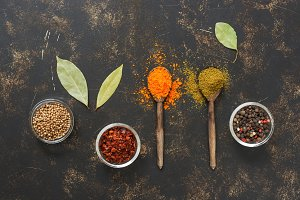 Spices on a dark background with wooden spoons.