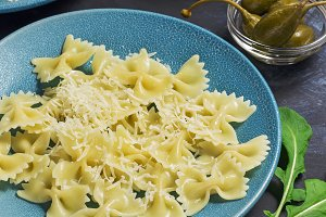 Pasta are on a blue plate with olives and capers on a dark background.