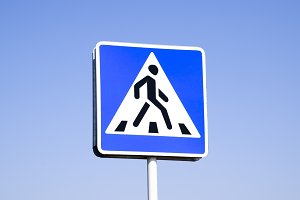 A pedestrian crossing sign. Sign on a blue sky background.