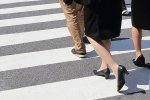 people legs crossing street