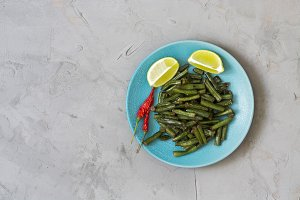 Stewed green beans served in a blue plate on a gray concrete background.