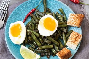 Stewed green beans with soft-boiled eggs, lime, toast, a glass of cold water.