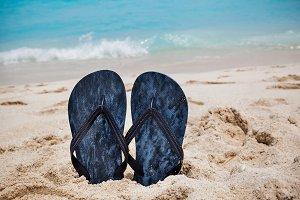 Closeup Of Flip Flops On Sandy Beach