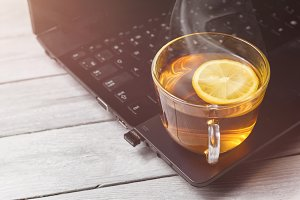 cup of tea with lemon on laptop and white wooden background, concept of tea time, relax with copy space