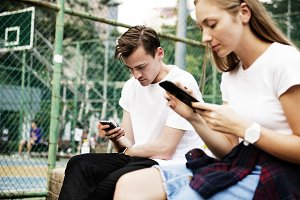 Couple in the park using smartphones