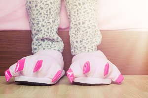 Female legs in cute pink monster foot slippers