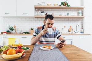 Young man sitting at table in the kitchen with a cup of coffee using mobile phone.