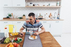 Man eating breakfast using smart phone in kitchen at home.