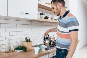 Young man prepare breakfast with tea pour water from kettle in kitchen.
