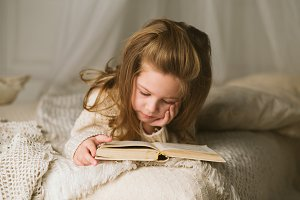Little cute girl reading a book